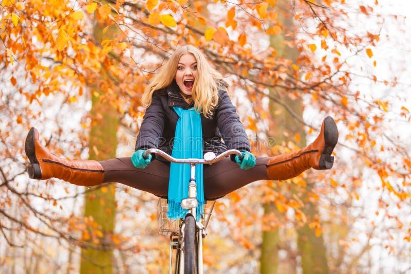 Actieve vrouw die pret berijdende fiets in de herfstpark hebben royalty-vrije stock afbeeldingen