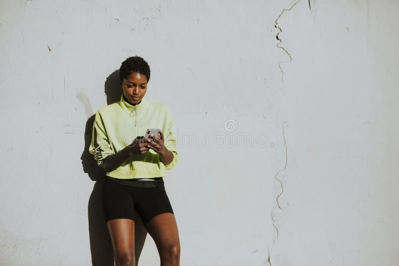 Actieve vrouw die zich door een witte muur bevinden stock afbeelding