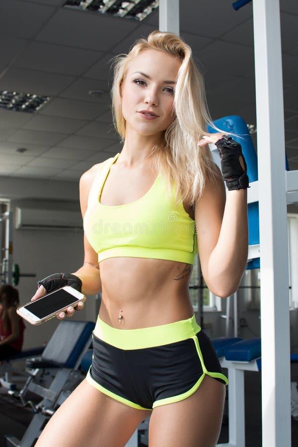 Actieve vrouw in sportkleding die slimme telefoon in de gymnastiek met behulp van Word beter De sterkte van zal Mooi lichaam stock fotografie
