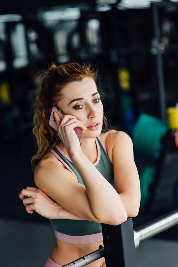 Actieve vrouw in sportkleding die telefoon in de gymnastiek met behulp van stock foto's