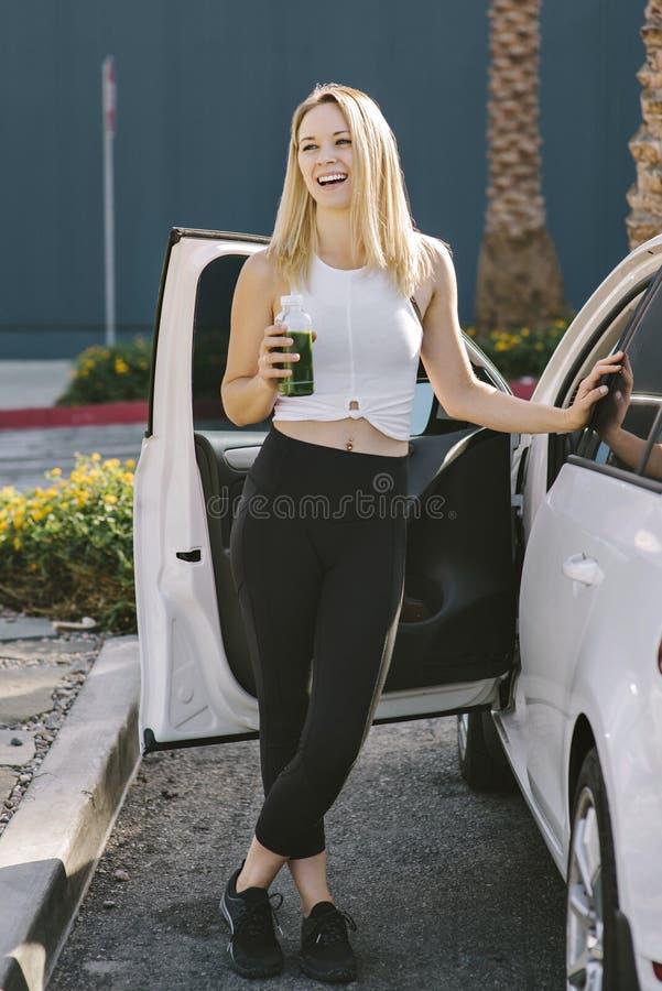 Actieve Vrouwelijke Blonde Millennial Glimlachen terwijl het Drinken van Groen Juice Happy Smiling After Workout royalty-vrije stock foto's