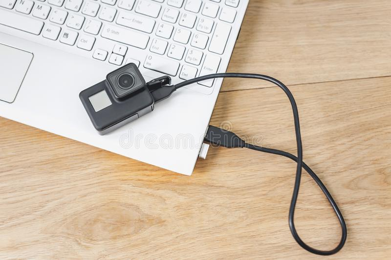 Action camera connected to a white laptop, against the background of a wooden table. stock photo