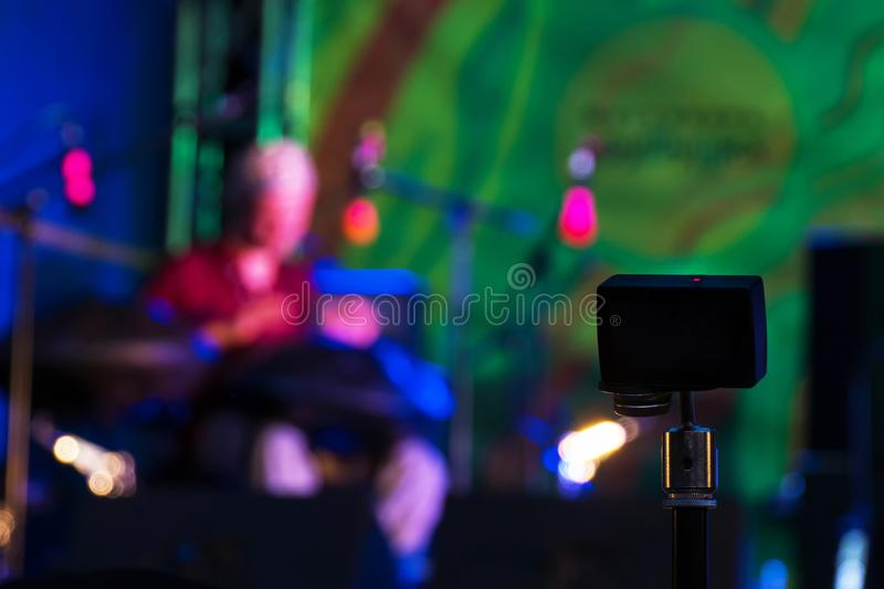 Action camera recording open air concert. Little action video camera recording ethnic open air concert. Man with tank drum or hang on blurry abstract bokeh royalty free stock images