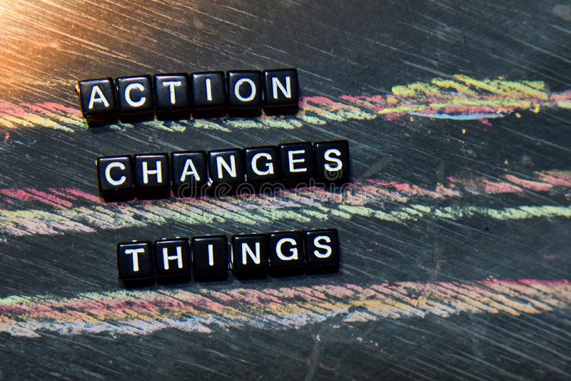 Action Changes Things - ACT on wooden blocks. Cross processed image with blackboard background. stock images