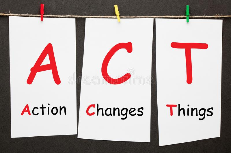Action Changes Things. ACT written on set stickers with clip hanging on a rope on black background royalty free stock photo