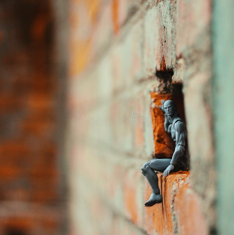 Action Figure on a Hole of Brick Wall royalty free stock image