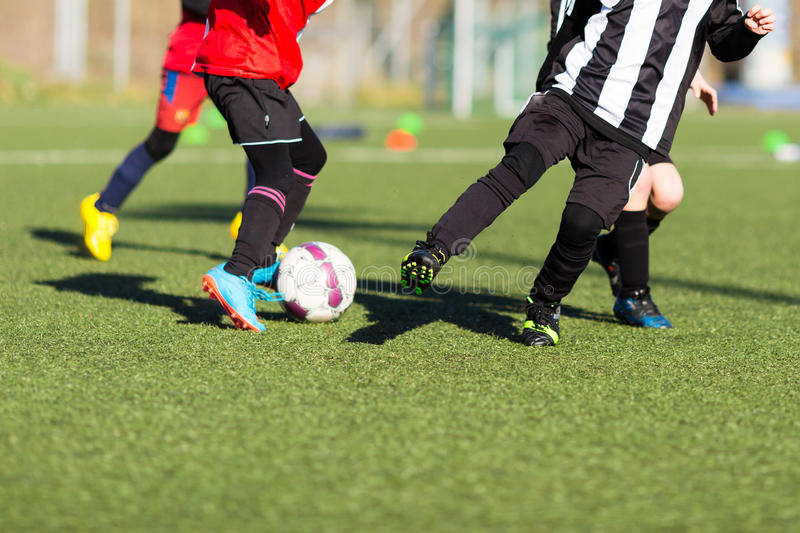 Action during kids soccer match. Young kids playing a soccer training match outdoors on an artificial soccer pitch royalty free stock photos