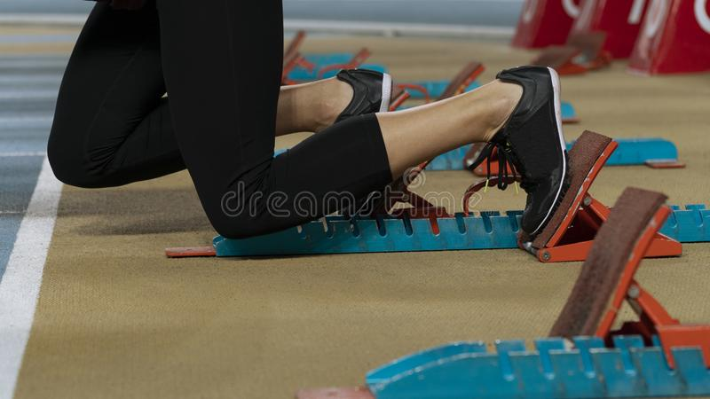 Action packed image of a female athlete leaving the starting blocks royalty free stock photo