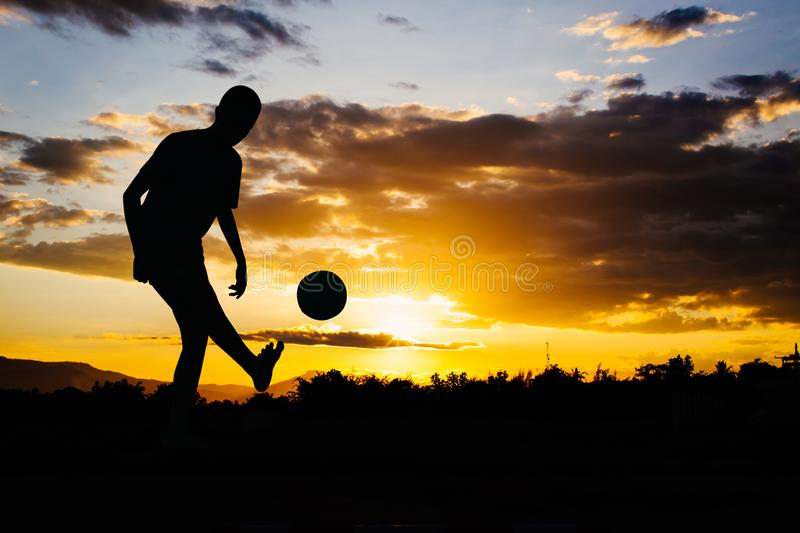 An action picture of a group of kids playing soccer football for exercise in community rural area under the sunset. royalty free stock photography