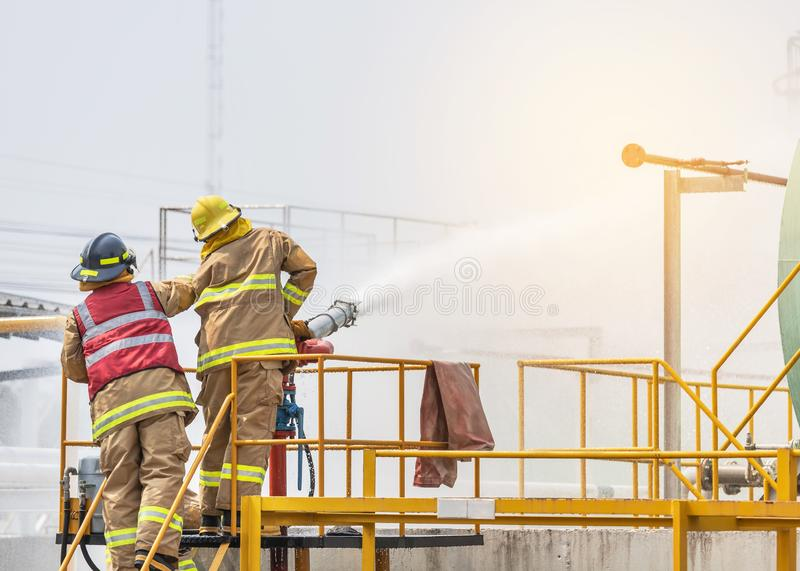 Firemans in yellow fire fighter uniform holding fire hose nozzle spraying foam water control fighting. Action professional firemans in yellow fire fighter royalty free stock photos