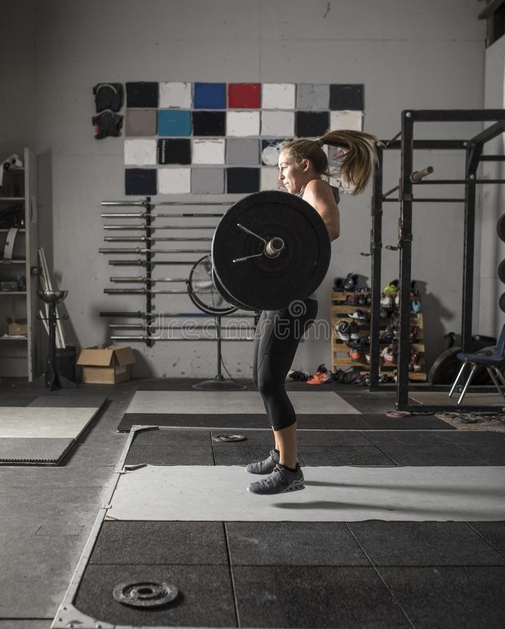 Action shot of female power lifter doing clean and jerk with heavy weights in gym stock photo
