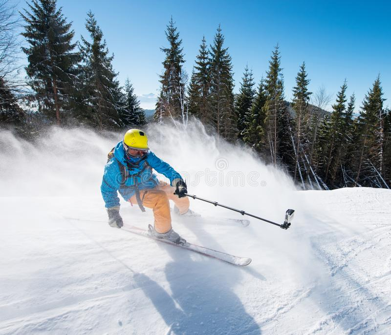 Action shot of professional skier taking selfies photo with a camera on selfie stick while skiing stock photos