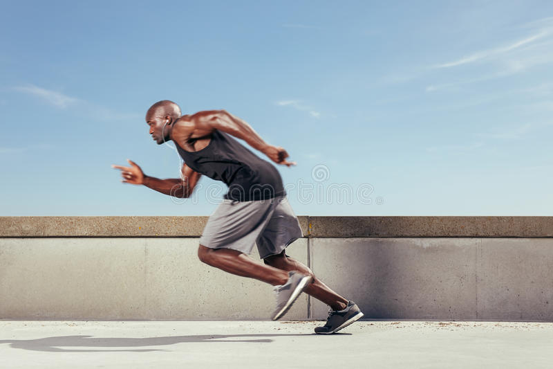 Action shot of a sporty young man running outdoors. Man start running on the pathway with the blue sky in the background and copy space around him. Motion blur royalty free stock image