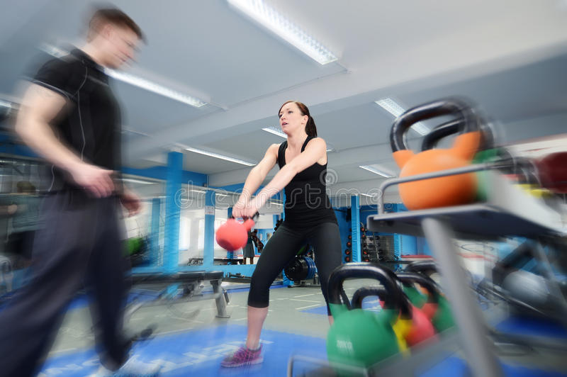 Action shot of woman exercising with kettle bell. Young women working out with kettle bell weights, with personal trainer in gym stock image