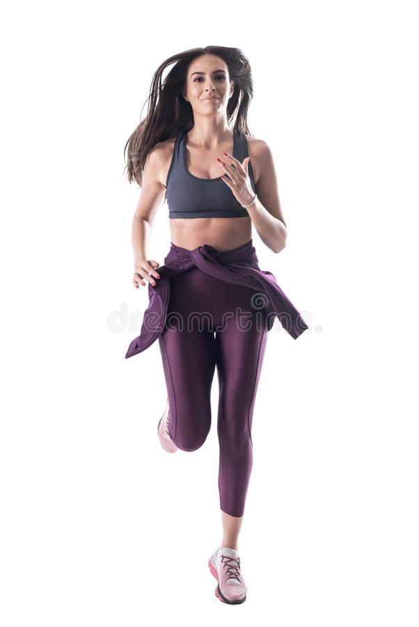 Action shot of young attractive fit woman athlete running and looking at camera. royalty free stock image