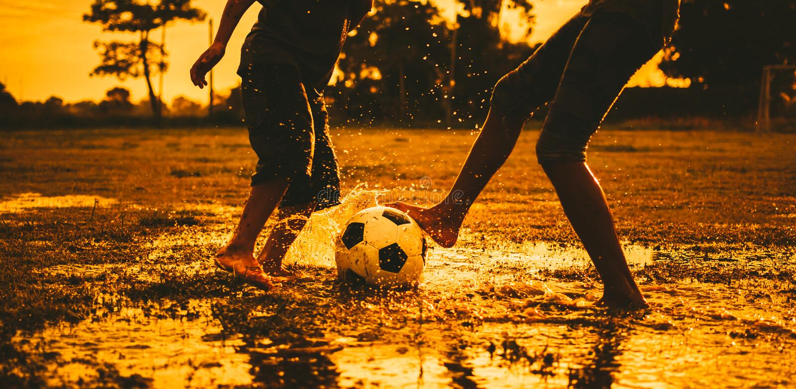 Action sport outdoors of a group of kids having fun playing soccer football for exercise in community rural area under the twiligh royalty free stock image