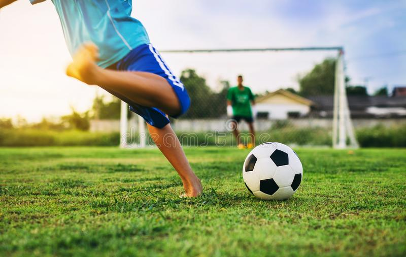 An action sport picture of a group of kids playing soccer football for exercise in community rural area royalty free stock photos