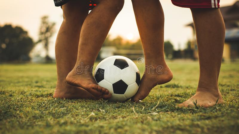 Action sport picture of a group of kids playing soccer football for exercise in community rural area under the sunset. royalty free stock photo