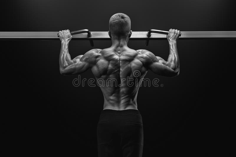 Actionnez le type musculaire de bodybuilder faisant des pullups dans le gymnase Homme de forme physique image libre de droits