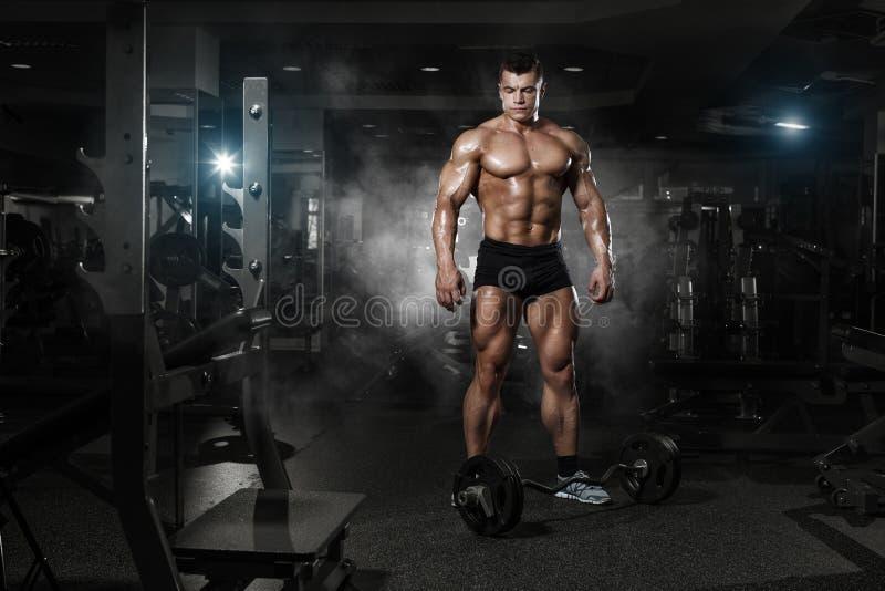 Actionnez très le type sportif se tenant avec la séance d'entraînement de barbell dans le gymnase images stock