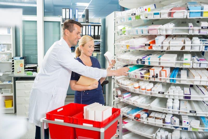 Actions heureuses d'And Assistant Counting de pharmacien dedans photo stock