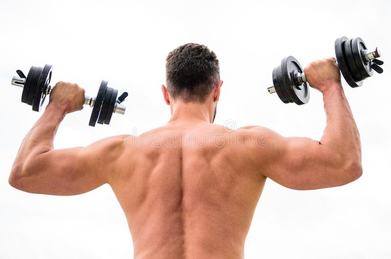 Actions speak louder than coaches. Dumbbell exercise gym. Muscular man exercising with dumbbell rear view. Sportsman royalty free stock photos