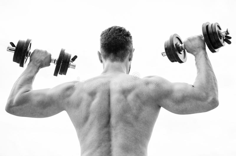 Actions speak louder than coaches. Dumbbell exercise gym. Muscular man exercising with dumbbell rear view. Sportsman stock photo