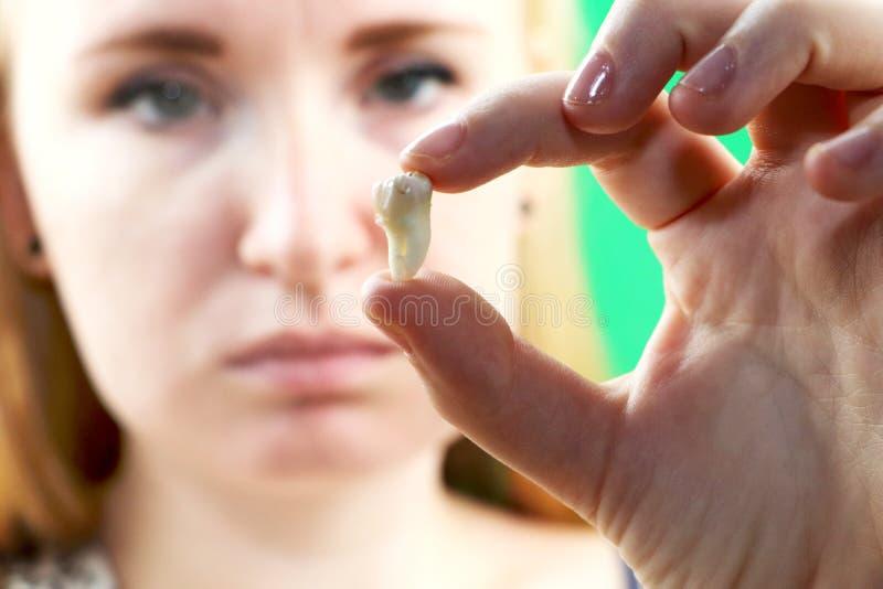 Actitud borrosa de una mujer con dolor de muelas y de una mano que sostiene el diente extraído, hocus en la mano fotos de archivo