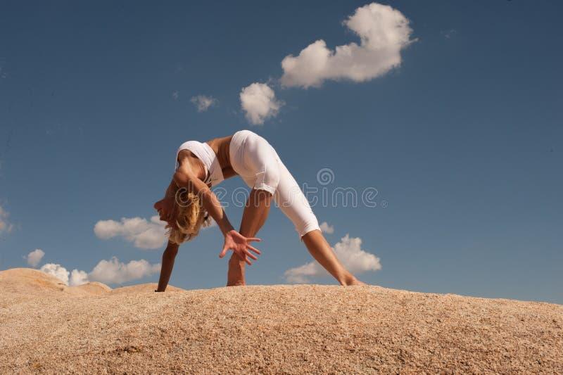 Actitud de la rueda de la mujer de la yoga del desierto imagen de archivo libre de regalías