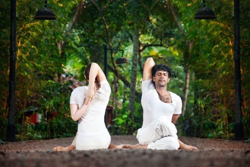Actitud de la vaca del gomukhasana de la yoga de los pares fotografía de archivo