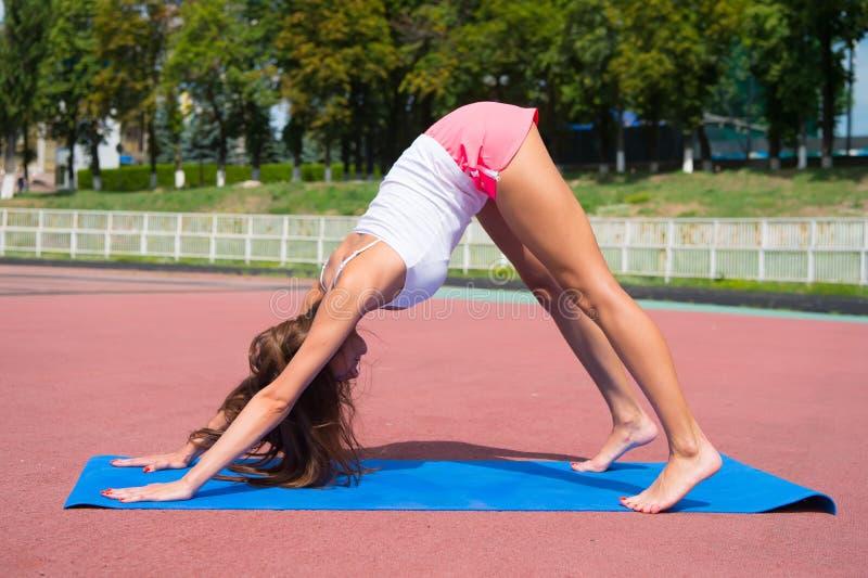 Actitud de la yoga del entrenamiento de la mujer en la estera de la aptitud fotos de archivo