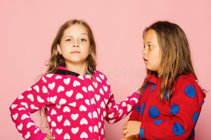 Actitud de los niños en fondo rosado Muchachas en pijamas brillantes coloridos foto de archivo libre de regalías