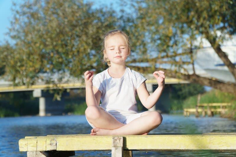 Actitud de Lotus de la yoga del bebé una yoga practicante del niño al aire libre imagenes de archivo