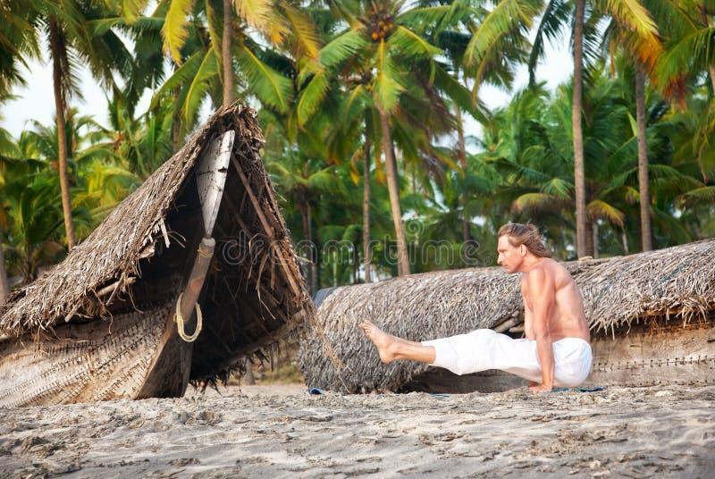 Actitud del angusthasana de la yoga en la playa imágenes de archivo libres de regalías
