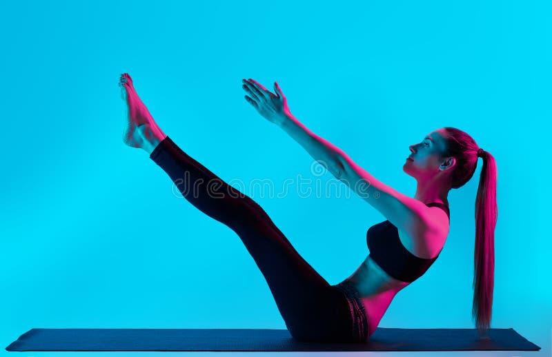 Actitud del barco de Navasana de los exercices de la yoga de la mujer foto de archivo libre de regalías