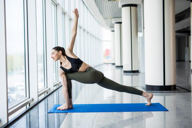 Actitud extendida del ángulo lateral La mujer atractiva joven hace ejercicio de la yoga en el gimnasio contra ventana imágenes de archivo libres de regalías