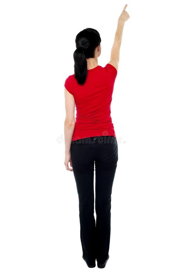 Actitud posterior de la mujer en casuals que señala lejos fotografía de archivo