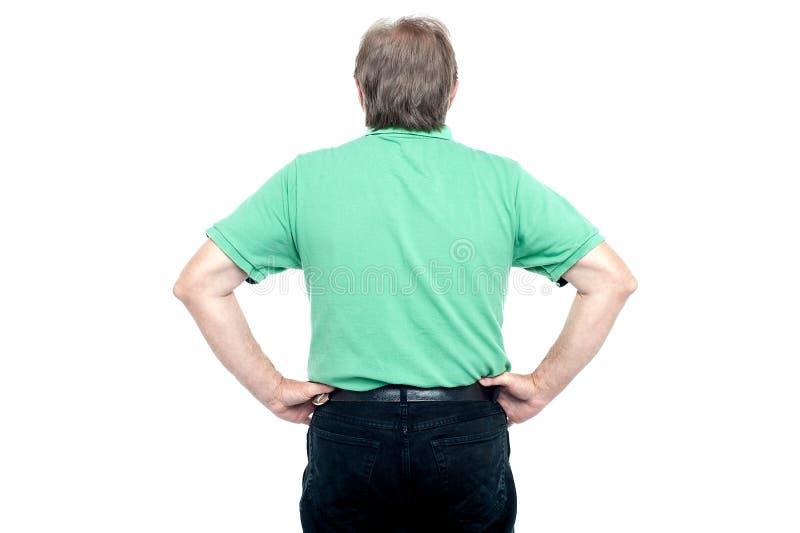 Actitud posterior del individuo mayor con las manos en su cintura imagen de archivo