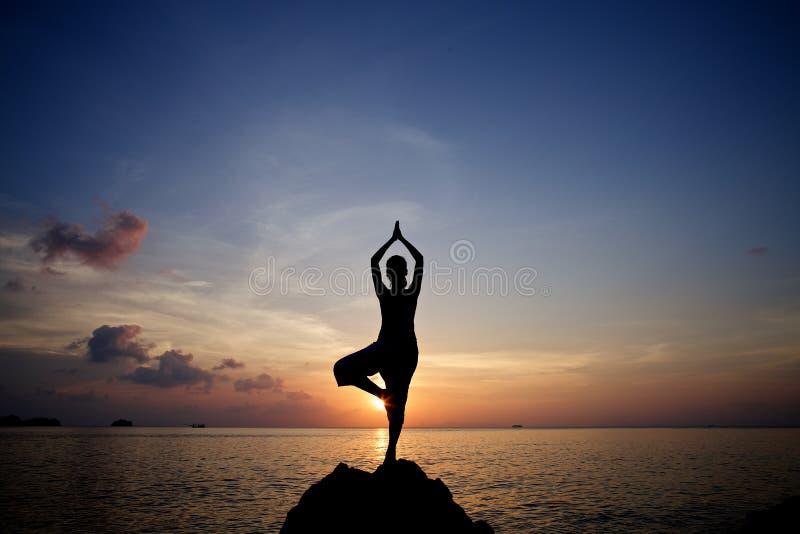 Actitud practicante de la yoga de la meditación de la mujer joven de la silueta en la playa tropical fotografía de archivo libre de regalías