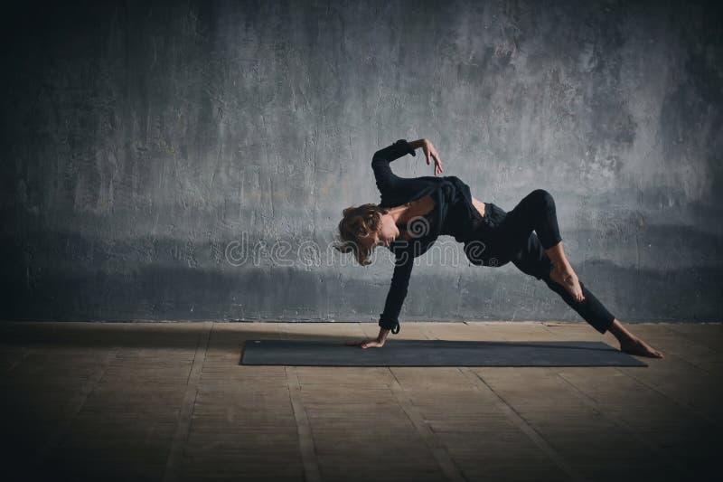 Actitud salvaje de la cosa del ajuste del yogini de la mujer de las prácticas del asana deportivo hermoso de la yoga en el pasill imágenes de archivo libres de regalías