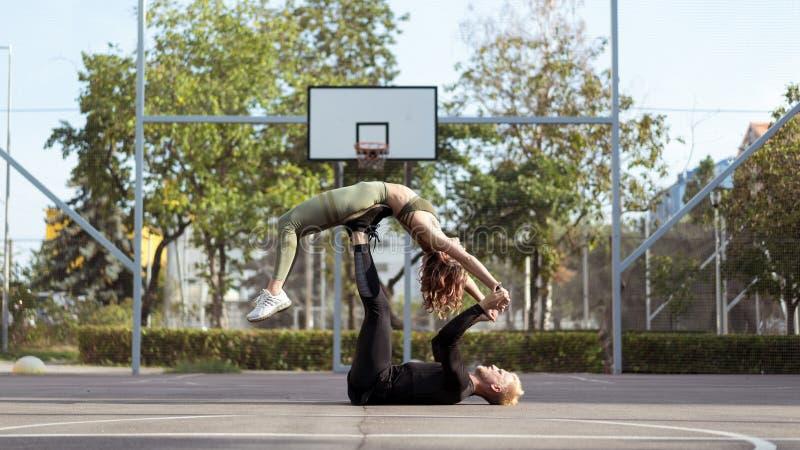 Actitudes ayudadas Yoga practicante de amor del hombre y de la mujer de Appearling y fuerza cada vez mayor del cuerpo fotos de archivo