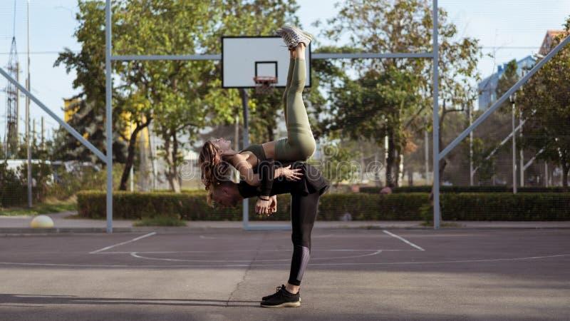 Actitudes ayudadas Yoga practicante de amor del hombre y de la mujer de Appearling y fuerza cada vez mayor del cuerpo foto de archivo libre de regalías