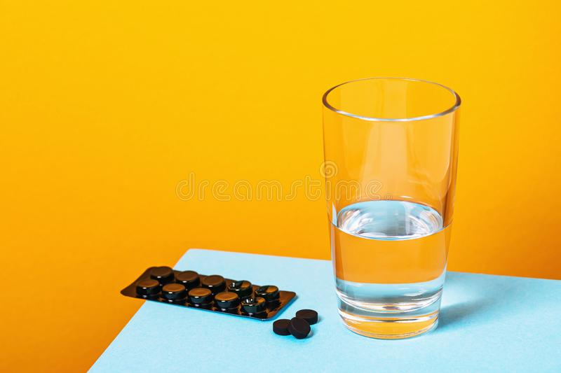 Activated carbon tablets and a glass of water on the table. Food Poisoning Treatment stock images
