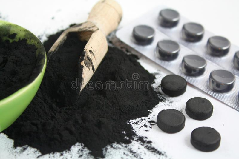 Activated charcoal black powder tablets pills absorbent. Photo royalty free stock photography