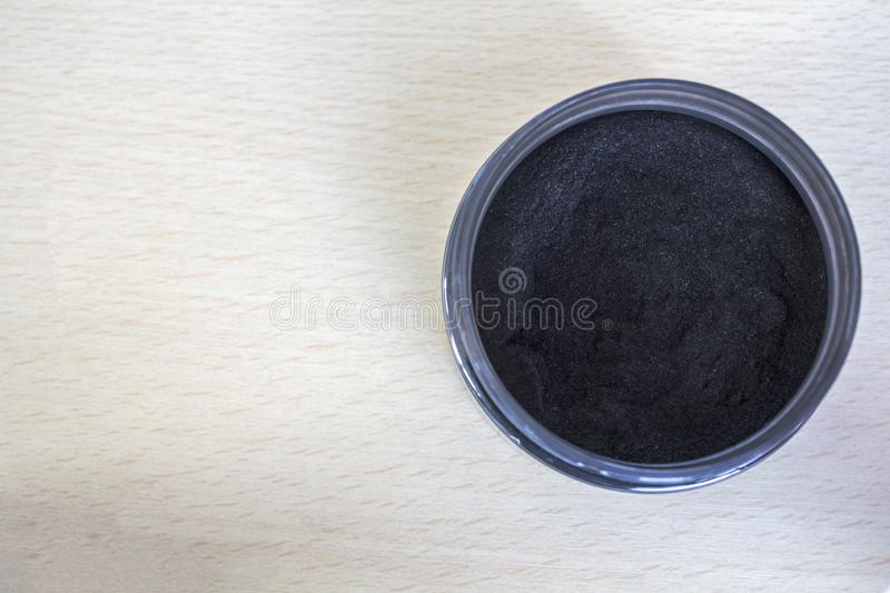 Activated charcoal powder on jar. Top view with copy space. Activated charcoal powder on jar with copy space royalty free stock photography