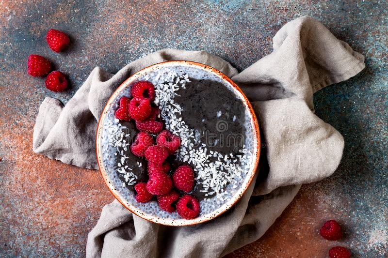 Activated charcoal smoothie and chia seed pudding bowl, vegan detox dessert with raspberry and coconut milk. Overhead, top view. Flat lay royalty free stock images