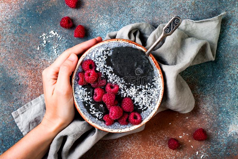 Activated charcoal smoothie and chia seed pudding bowl, vegan detox dessert with raspberry and coconut milk. Overhead, top view. Flat lay stock photography