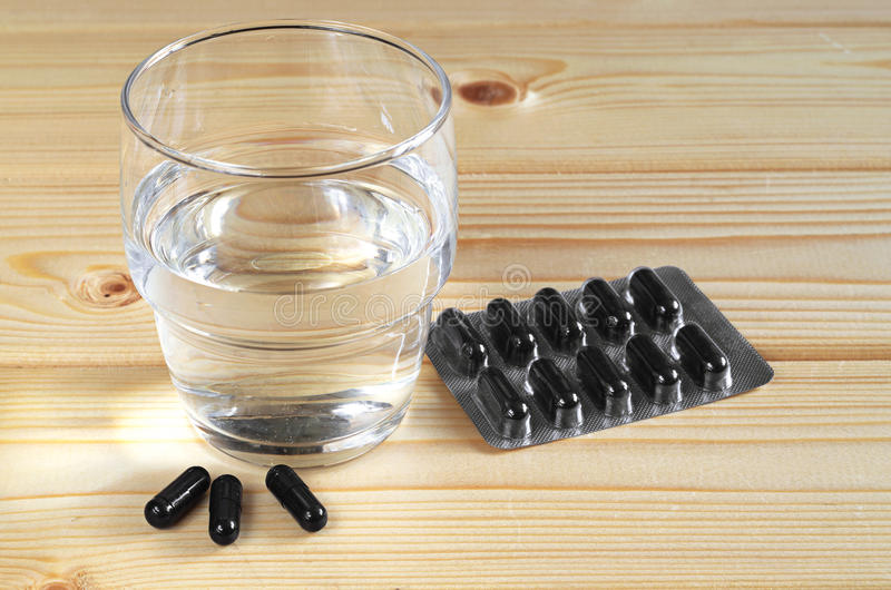 Activated charcoal and water. Medical capsules with activated charcoal and glass of water on wooden table stock photos