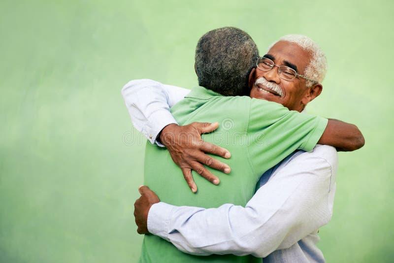 Старые други, 2 старших люд афроамериканца встречая и обнимая стоковое фото rf