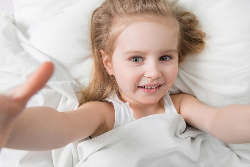 Active adorable child awake, soft white sheets royalty free stock photography